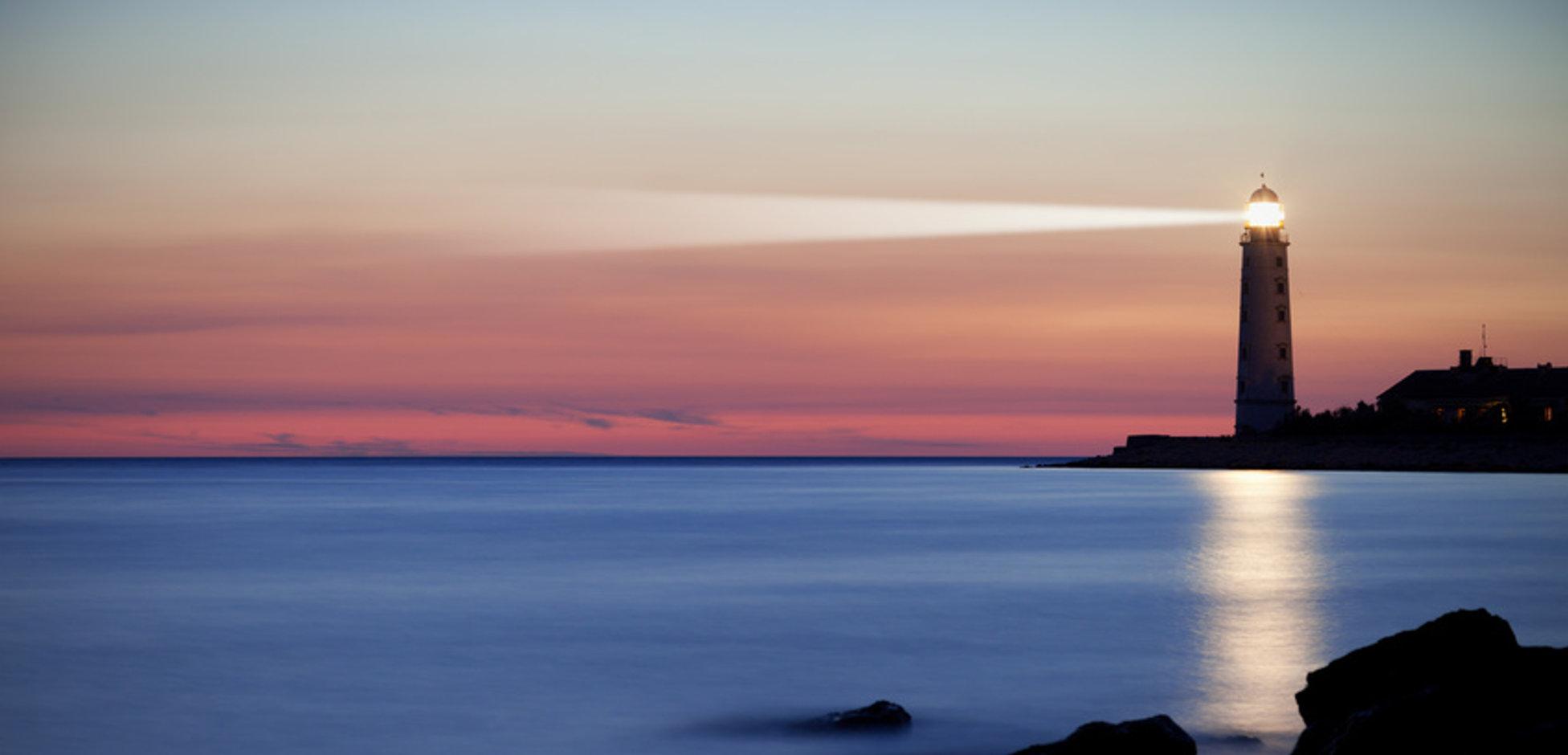 Seascape at sunset. Lighthouse on the coast
